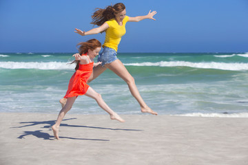 Mother and daughter leaping, with arms outstretched, on sunny beach