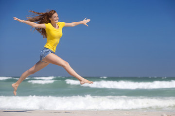 Happy woman leaping in air on sunny beach