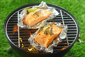 Two gourmet salmon cutlets grilling on a fire