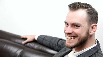 Young businessman sitting down laughing