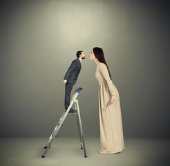 woman kissing small man