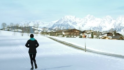 Woman running in cross country road on winter