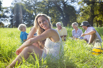 Portrait of smiling woman and having picnic in treelined field