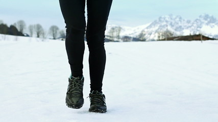Feet of young woman jogging on the snow