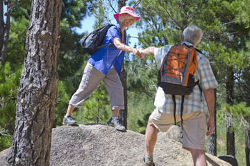 Senior couple helping each other hiking on mountain path