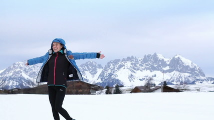 Young beautiful woman rotates in winter scenery, slow motion