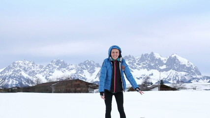 Young happy woman jumping on the snow field, slow motion