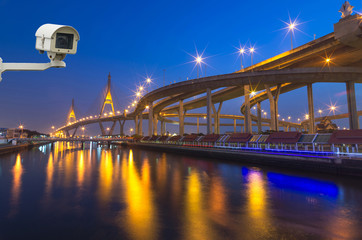 Security camera monitoring the Bhumibol Bridge with river at twi