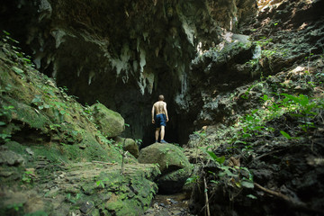 Man looking into empty limestone cave