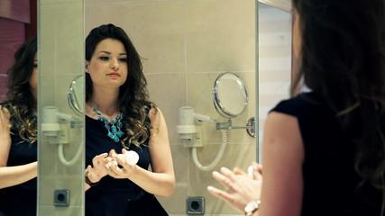 Pretty, elegant woman applying antiperspirant on her armpit