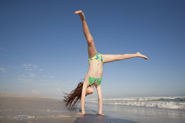 Redheaded Girl doing handstand on sunny beach