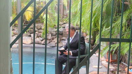 Businessman walks and sits by a pool through the bars of fence