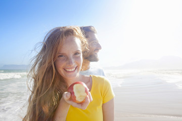 Smiling couple on sunny beach, with woman holding an apple