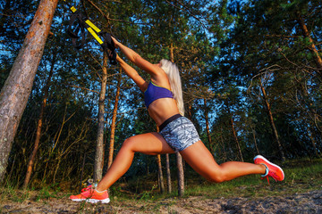 Tough young woman in sports clothing doing fitness