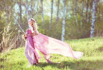 Beautiful blonde girl in a pink dress
