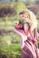 Peautiful blonde girl in a pink dress with a bouquet of flowers