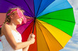teen girl standing with umbrella on the blue sky background
