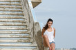 Woman sitting on cement stairs - 78412734