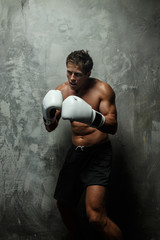 Awesome male boxing on grey background.