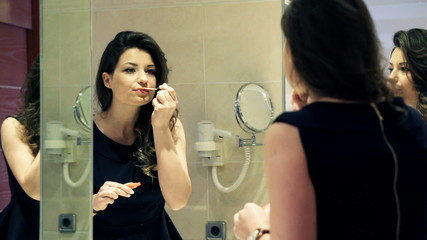 Pretty, elegant woman applying lip gloss in front of the mirror