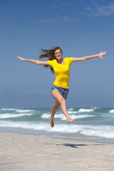 Happy woman, with arms outstretched, leaping in air on sunny beach