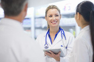Doctor, wearing stethoscope, with digital tablet, talking to colleagues