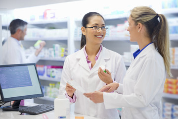 Pharmacist, holding prescription, smiling and talking to colleague in pharmacy