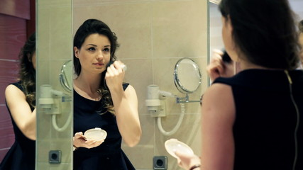 elegant woman applying powder on her face with brush