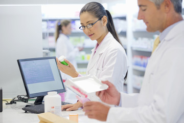 Pharmacists counting and inspecting medication behind pharmacy counter