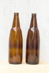 two amber beer bottle on concrete wall background