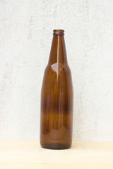 single amber beer bottle on concrete wall background