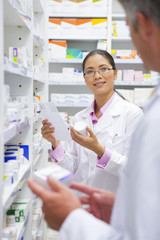 Pharmacist holding medication pack and prescription, talking to colleague in pharmacy