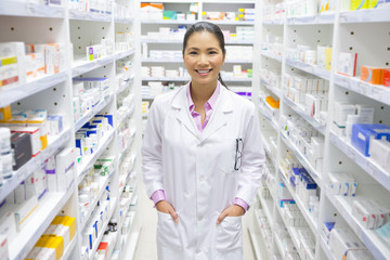 Pharmacist, with hands in pockets, in pharmacy