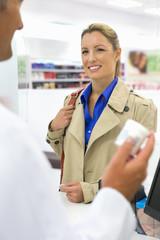 Smiling Female customer purchasing medication from pharmacist