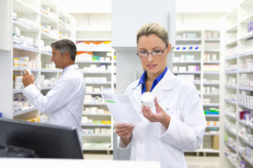 Pharmacist inspecting medication and prescription behind pharmacy counter