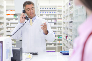 Pharmacist on telephone, reading label on back of medicine pot