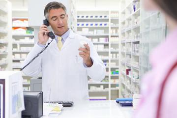 Pharmacist on telephone, reading label on back of medicine pot