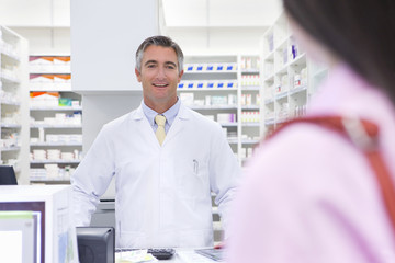 Pharmacist smiling at customer from behind pharmacy counter