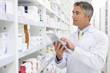 Pharmacist with digital tablet looking for medication on pharmacy shelf