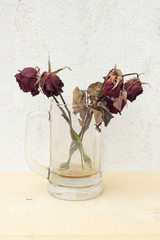 sear red rose in glass on plywood background and concrete wall