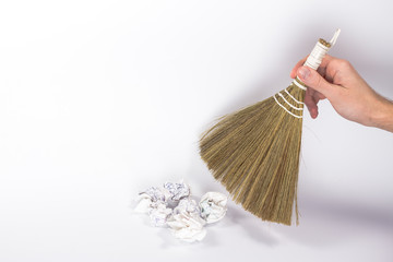 isolated broom in a man's hand and paper ball