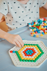 prescholer child playing colorful mosaic at home
