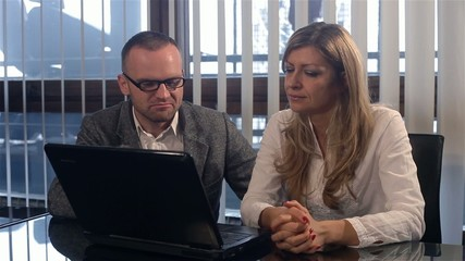 Young man and woman using laptop in the office,business people