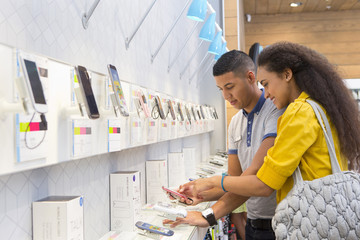 Store assistant helping female customer in phone store