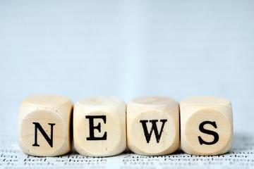 Holzwürfel mit dem Wort News auf einer Zeitung