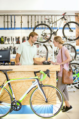 Store manager assisting customer in bicycle shop