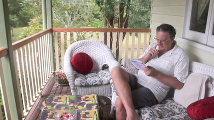Mature man sitting and relaxing on his verandah playing sudoku.