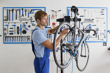 Cycle technician repairing bicycle