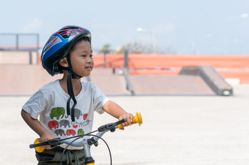 Little boy wearing helmets ridding bike .