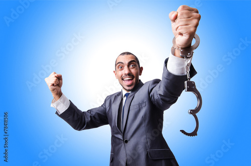 Funny businessman with handcuffs on white - 78418506